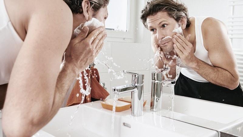 Mann wäscht sich Rasierschaum aus Gesicht